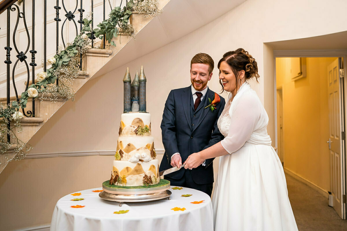 cutting the wedding cake at Eastington park wedding