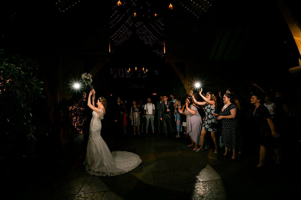 bride throws flowers at shustoke barn wedding